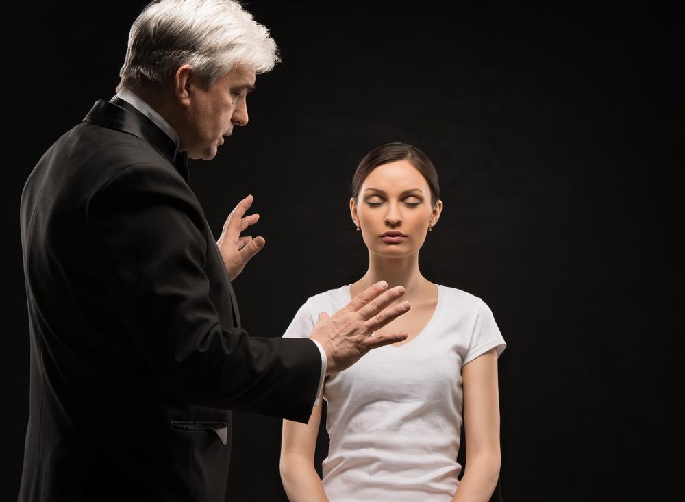 Мужчина погружает пациенту в гипноз.