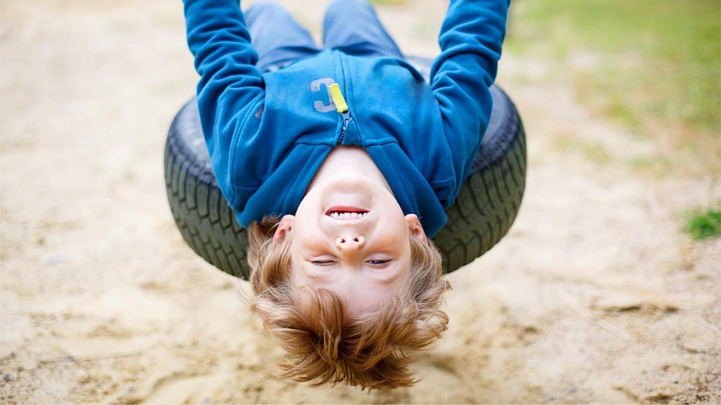 Мальчик катается на качелях