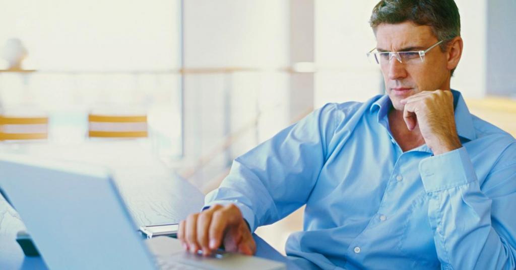 Мужчина в очках сидит за компьютером.