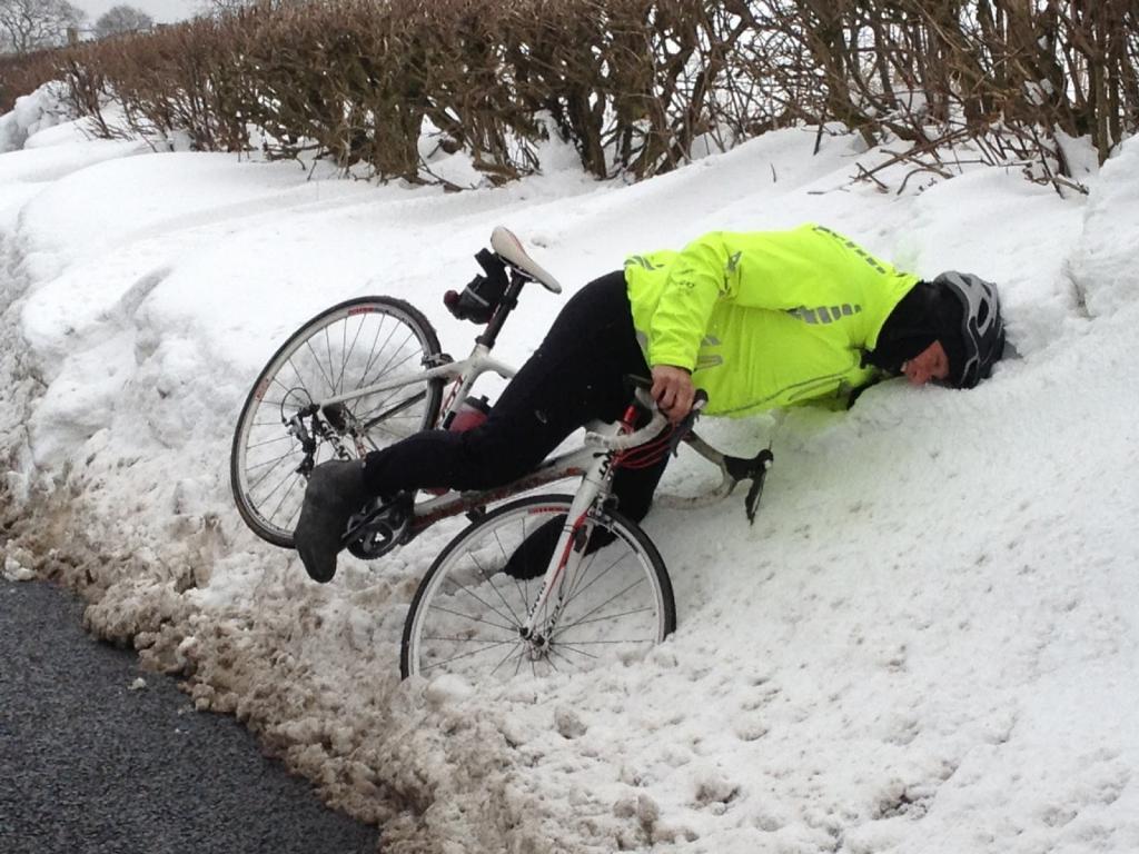 Велосипедист упал в снег.