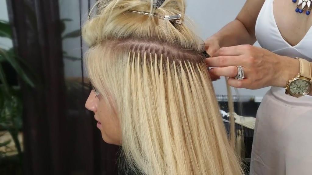 парикмахер наращивает волосы клиенту