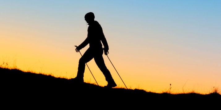 человек с палками поднимается в гору