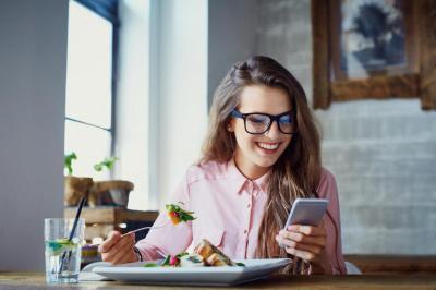 Девушка просматривает сообщения за обедом