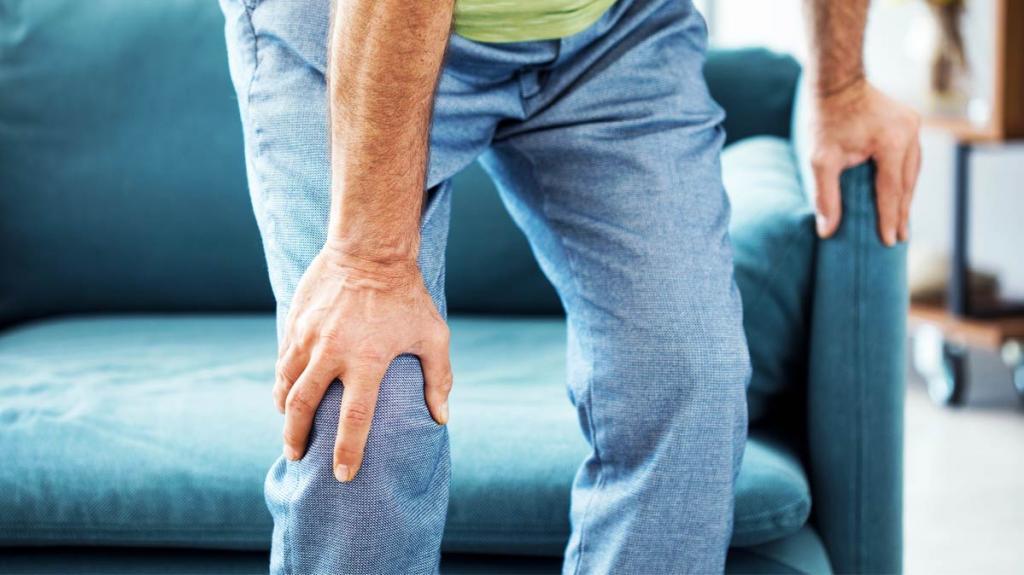 мужчина держится рукой за колено