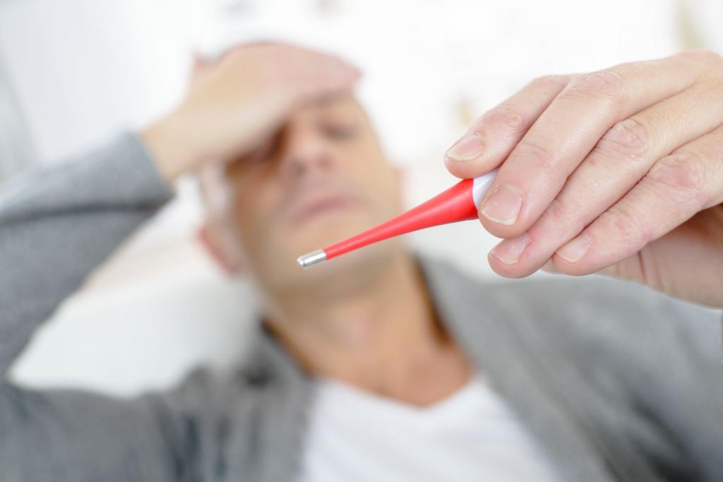 мужчина измеряет температуру