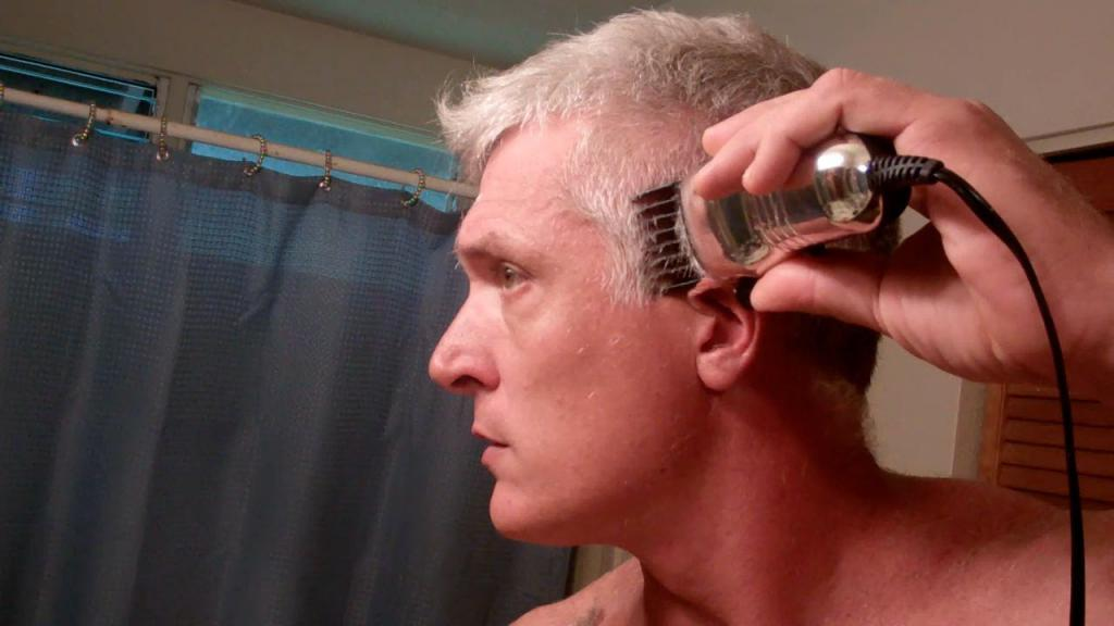 Мужчина подстригает волосы сам себе машинкой