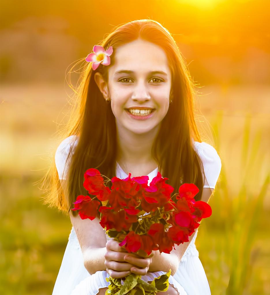 Милая девочка с цветком в волосах