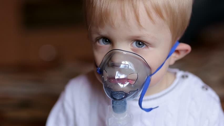 Ребенок дышит с маской