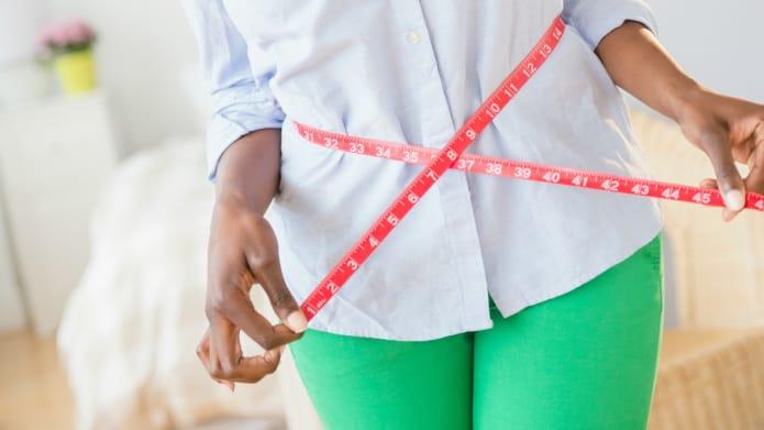 женщина с сантиметром на поясе