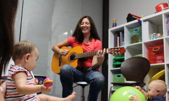 женщина играет на гитаре перед детьми