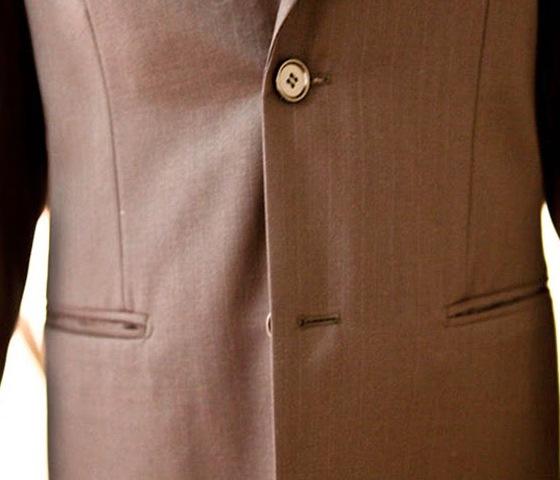 Незастегнутая пуговица пиджака.