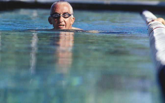 мужчина в очках плывет в бассейне