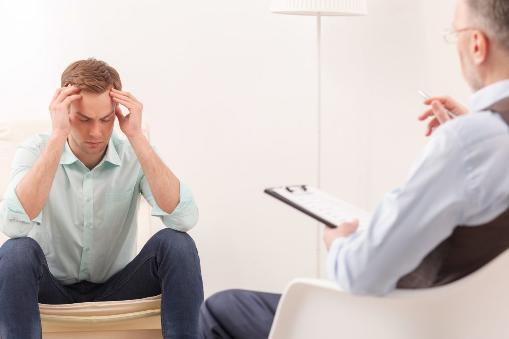мужчина беседует и держится за голову