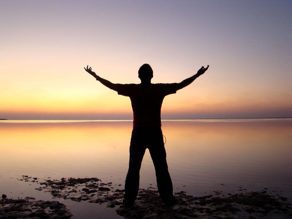 Мужчина стоит на фоне заката