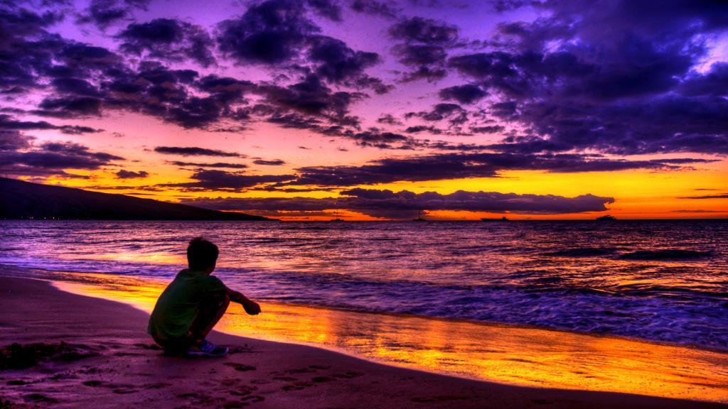 Мальчик сидит около океана