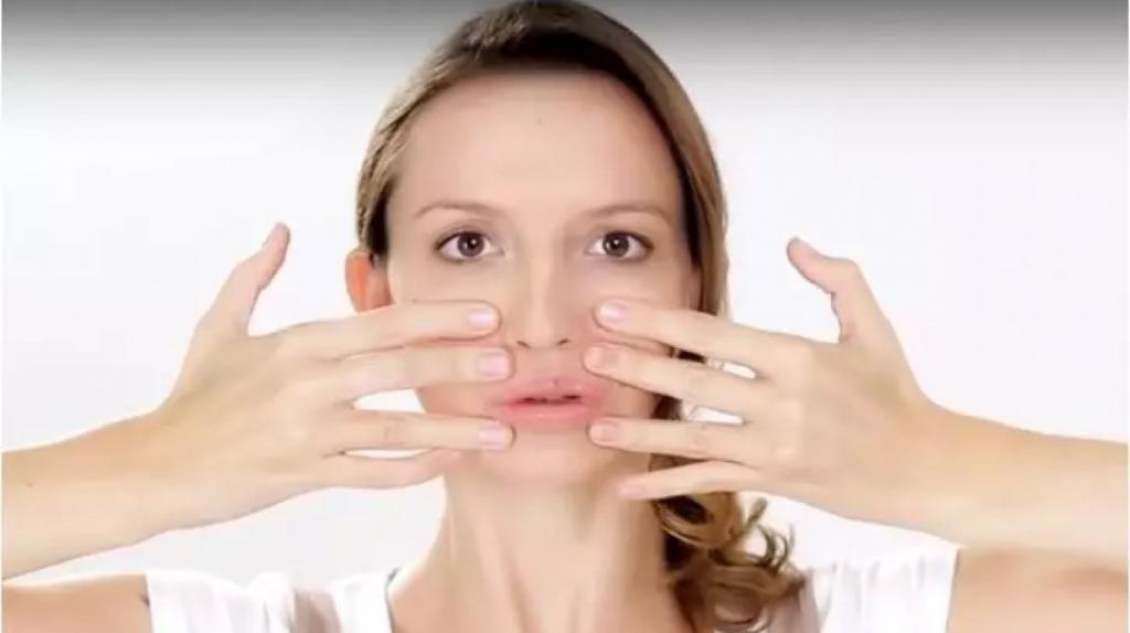 Девушка держит руки у лица