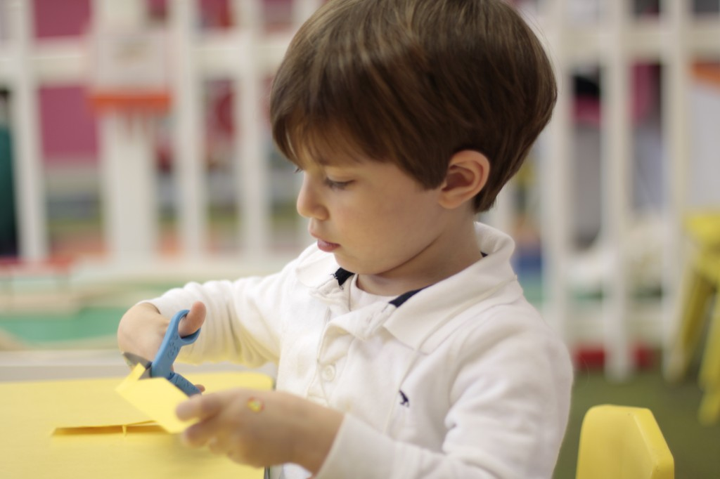 Ребенок пользуется ножницами