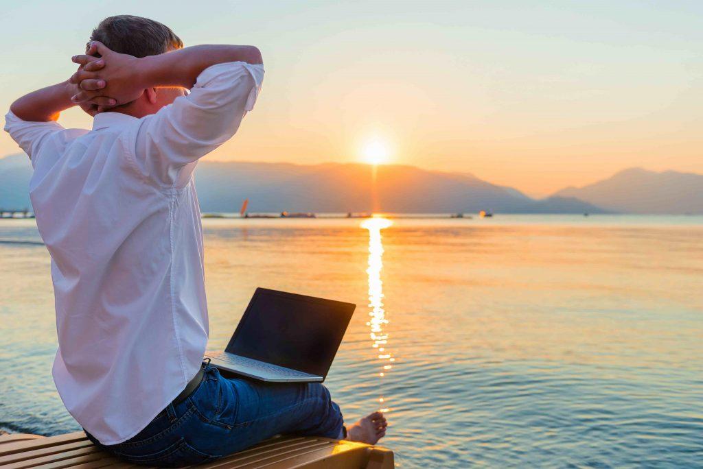 человек с ноутбуком на берегу