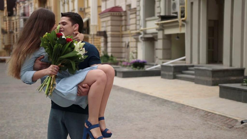 Мужчина держит девушку на руках