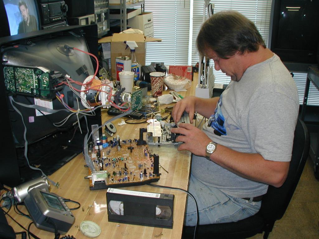 Мастер ремонтирует телевизор.