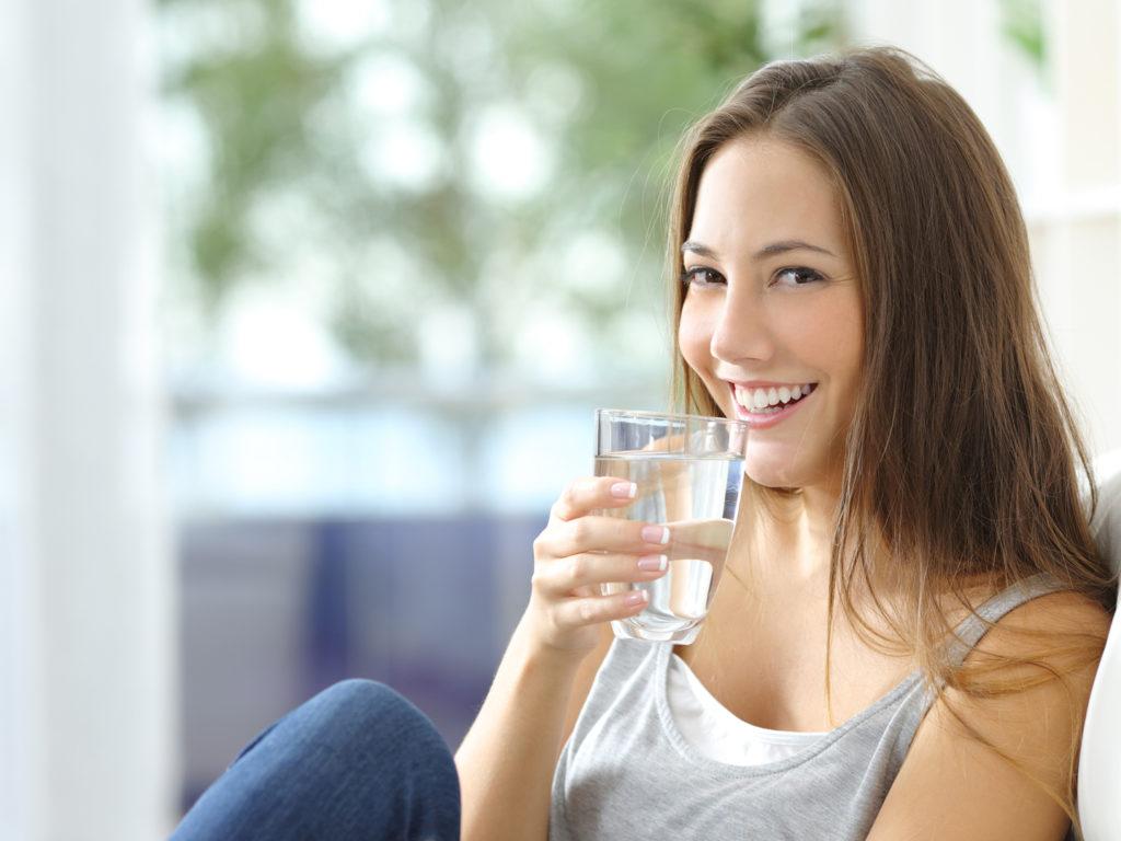 Девушка пьет минеральную воду